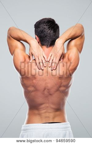 Back view portrait of a man with neck pain over gray background