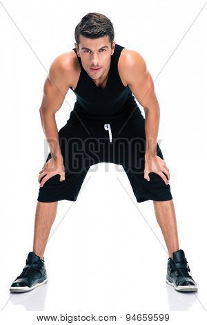 Full length portrait of a fitness man standing isolated on a white background. Looking at camera