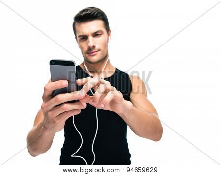 Sports man using smartphone with headphones isolated on a white background. Focus on smartphone