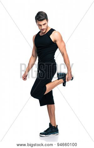 Full length portrait of a sports man stretching legs isolated on a white background