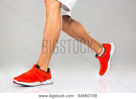 Closeup portrait of a sports male legs over gray background