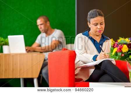 Young woman, taking notes and writing down ideasin a corporate lobby annex lounge on casual friday