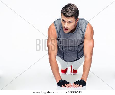 Fitness young man doing push ups isolated on a white background and looking away
