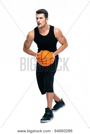 Full length portrait of a handsome man in sports wear playing in basketball isolated on a white background