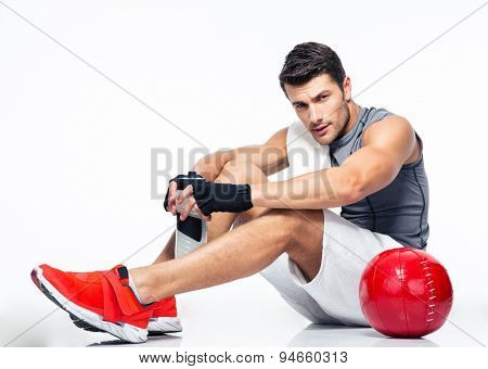 Fitness man resting on the floor isolated on a white background and looking at camera