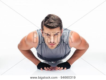 Fitness young man doing push ups isolated on a white background and looking at camera