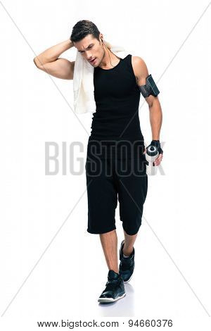 Full length portrait of a fitness man holding towel and bottle with water isolated on a white background