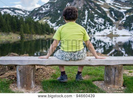 Kid sitting in mountain park