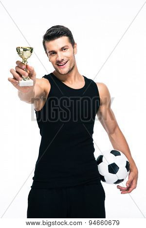 Happy football player holding winners cup isolated on a white background. Looking at camera