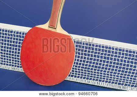 Table tennis racket and net on a table tennis table