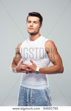 Pensive fitness man standing over gray background and looking away