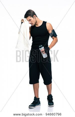 Full length portrait of a sports man holding towel and bottle with water isolated on a white background