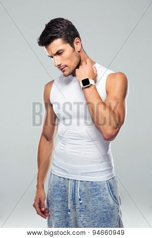 Portrait of a handsome fitness man standing over gray background