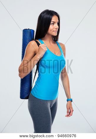 Fitness woman holding yoga mat over gray background. Looking away