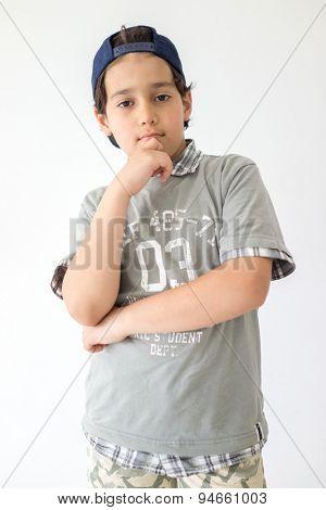 Cute boy posing on white wall