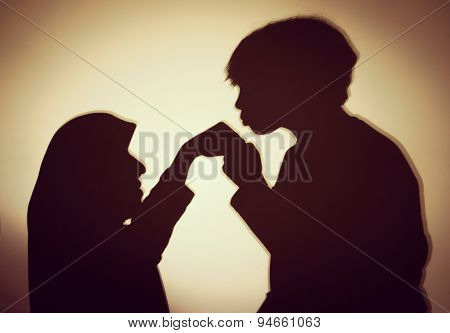 Silhouette of Muslim woman with her son