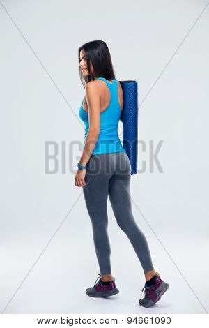 Back view portrait of a young fitness woman with yoga mat over gray background