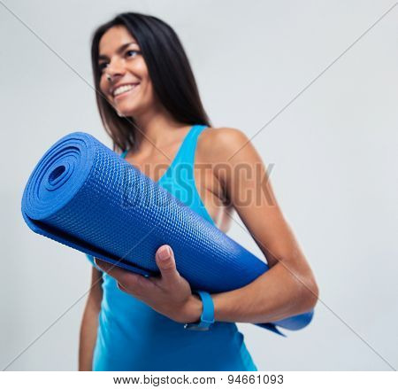 Smiling fitness woman holding yoga mat over gray background. Focus on mat