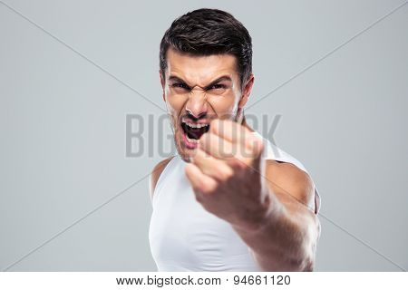 Angry man screaming and showing fist over gray background
