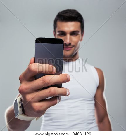 Fitness man making selfie photo on smartphone over gray background. Focus on smartphone