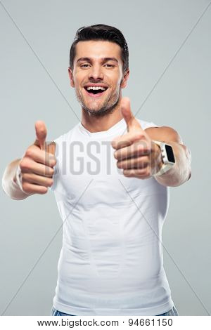 Cheerful fitness man showing thumb up over gray background