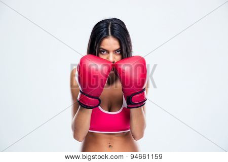 Sporty woman in boxing gloves looking at camera over gray background
