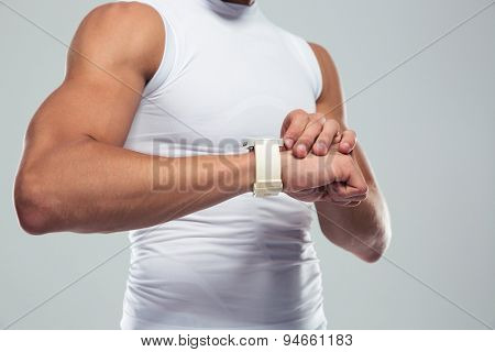 Closeup portrait of a muscular man using smartwatch over gray background