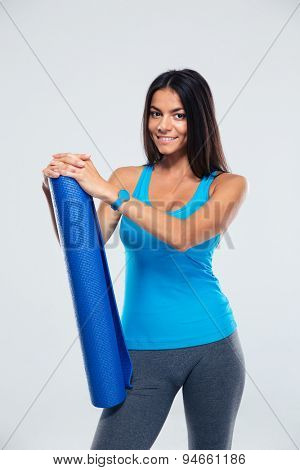 Happy sports woman holding yoga mat over gray background. Looking at camera