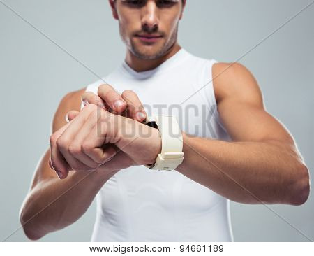 Closeup portrait of a fitness man using smartwatch