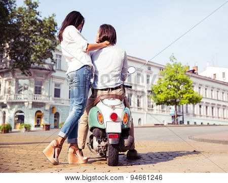 Portrait of happy young couple on scooter enjoying themselves in european city