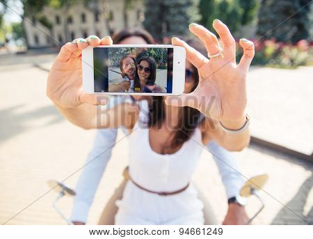 Happy couple showing smartphone screen while making selfie  outdoors