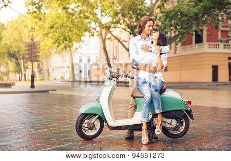 Happy beautiful couple on scooter in old european city