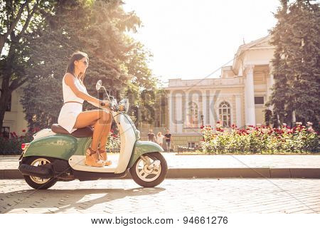 Young happy woman driving vintage scooter in old european town