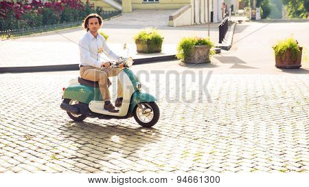 Young man riding a scooter in town