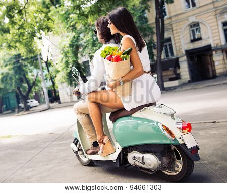 Happy young couple riding a scooter while woman holding a shopping bag full of groceries