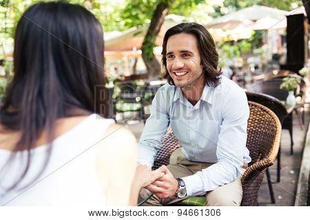 Happy man having romantic time with his girlfriend in city cafe