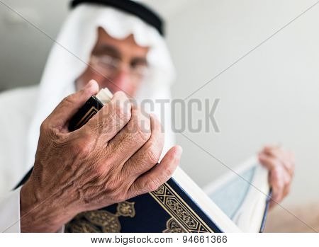 Elderly man sitting and reading book
