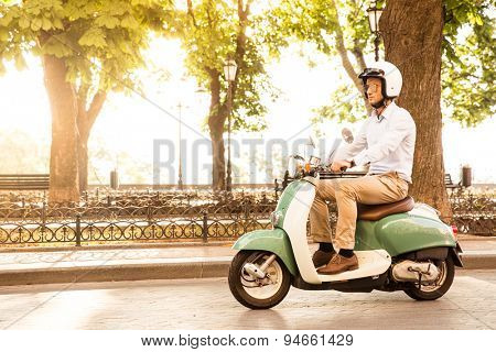 Trendy man driving a scooter in helmet. Sun is shining through trees on background