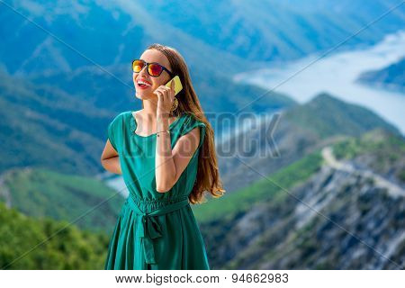 Woman with phone on the mountain