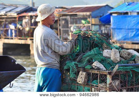 Nha Trang, Vietnam - October 22, 2011: A Fisherman Is Preparing His Fishing Net For A New Working Da