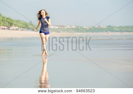 Young beautiful caucasion woman with brown hair runs along the beach on Bali close to sunset