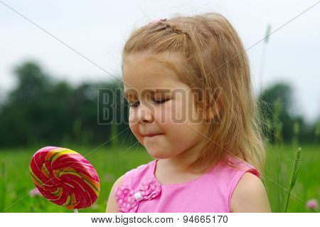 cute little girl eating a lollipop on the field