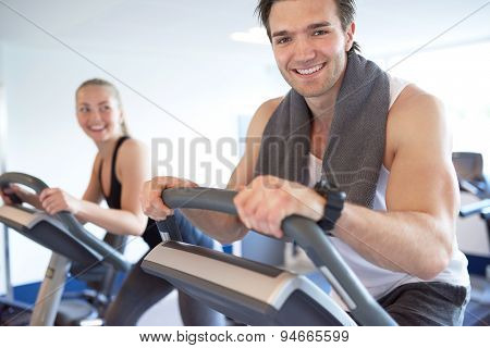Muscular Guy On Elliptical Bike Smiling At Camera