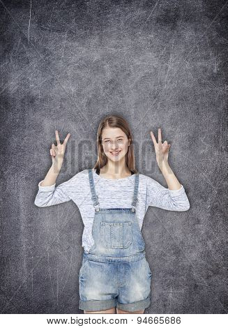 Happy Teenager Girl Showing Victory Sign On The Chalkboard Background