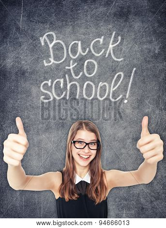 Happy Schoolgirl Showing Thumbs Up On The Chalkboard Background