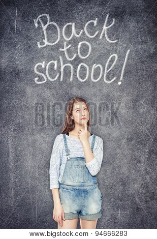 Teenage School Girl Looking Up On The Chalkboard Background