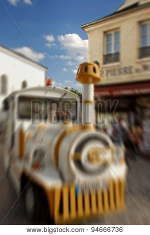 Abstract Background.  Small Train For Tourists Stops In Front Of Souvenir Stores. Blur Effect Defocu