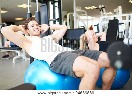 Young Fit Guy Doing Sit-ups On Exercise Ball
