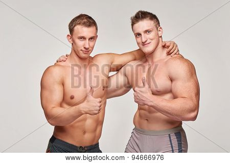 Two athletic men gesturing thumbs up