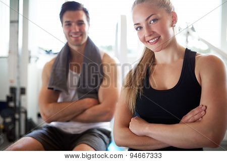 Fit Couple Smiling At Camera With Arms Crossed